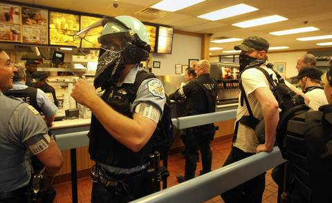 A Chicago police officer covering his face stands beside protester as they wait in line at a Burger King during the protests.