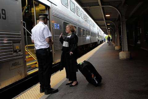 "Vicky Mitchell, right, from London, asks a conductor whether she can board a train at the Evanston Davis Street Metra station with her large bag. She was carrying sales samples of ""funky walking sticks."" The conductor said yes."