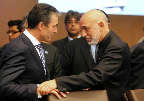NATO Secretary General Anders Fogh Rasmussen and Afghan President Hamid Karzai talk before a meeting of members of the International Security Assistance Force in Afghanistan.