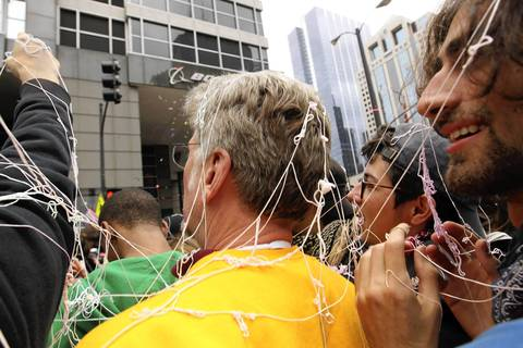 Protesters are covered with silly string as they rally in front of Boeing headquarters in Chicago during the NATO 2012 Summit.