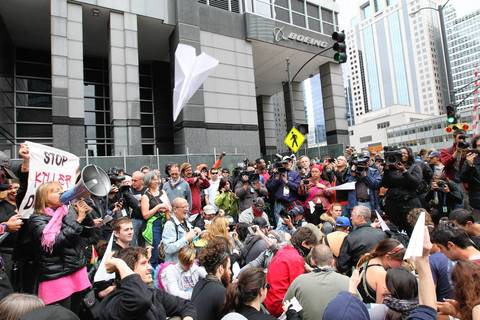Paper airplanes float over Occupy protesters as they rally in front of Boeing headquarters