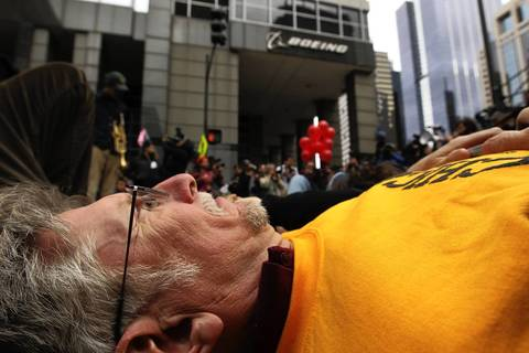 Protesters perform a die-in in front of Boeing headquarters.