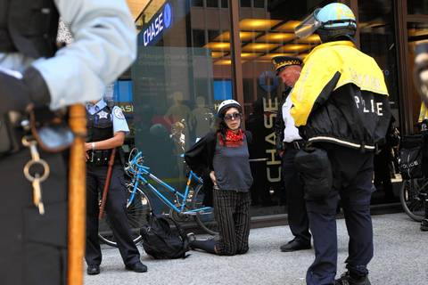 Police detain a protester with a backpack and bike during a march by Occupy.
