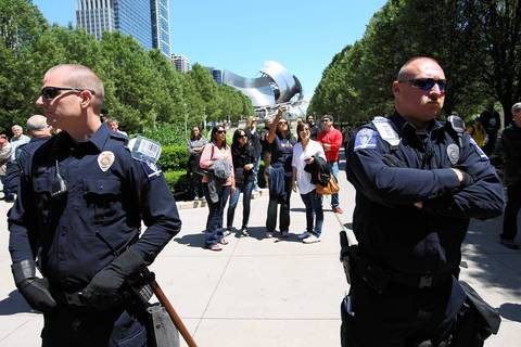 Police officers from Charlotte, N.C. are part of the line separating the protest march from tourists at Millennium Park.