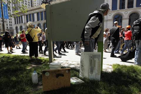 Galena artist Carl Johnson takes a break from painting to watch protest march pass on Michigan Avenue.