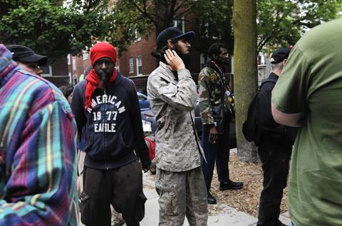 NATO protesters stand outside at their camp at the Wellington United Church of Christ, watching for Chicago police presence.