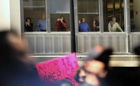 Office workers photograph the protesters as the march heads east on Washington Street.