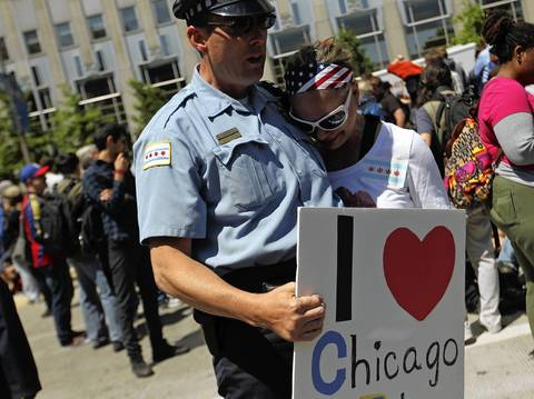 Protester Susann Doveikis-West hugs a Chicago Police officer during a demonstration in front of President Barack Obama's campaign headquarters.