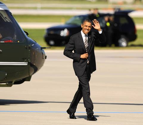 President Barack Obama waves to the press as he prepares to board Air Force One as he departs O'Hare International Airport after the conclusion of the NATO summit.