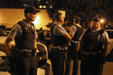 Police officers survey the area as protesters begin to board buses at North Lake Shore Drive and West Belmont Avenue.
