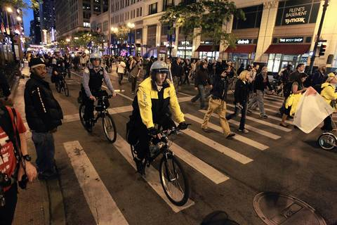 Police officers ride alongside protesters as they march on State Street in the Loop.