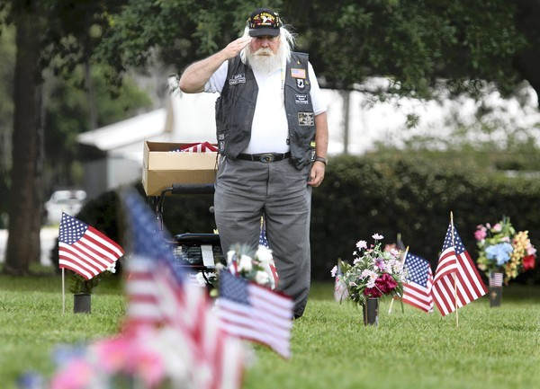 Army veteran Frank Schmidgall salutes at Woodlawn Memorial Park &amp; Funeral Home on Friday.