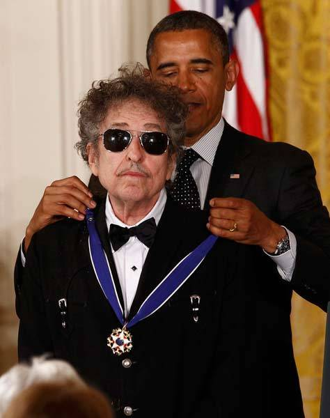 President Barack Obama awards a 2012 Presidential Medal of Freedom to musician Bob Dylan.