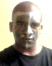 Alexander Kinyua is pictured in a photo he uploaded to blogtalkradio.com with his face in camouflage paint.