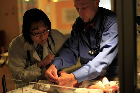 At Comer Children's Hospital, Sho Yano, 21, already a Ph.D. and soon to be an M.D., looks over a newborn patient with Dr. Darrel J. Waggoner, Associate Professor of Human Genetics and Pediatrics, in the Neonatal Intensive Care Unit.