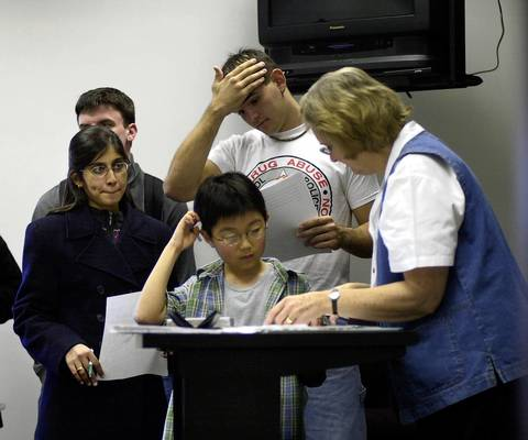 As classmates wait their turn, Sho Yano, 9, discusses a paper with his English teacher, Professor Claire Sanchez, at Loyola in 2000.
