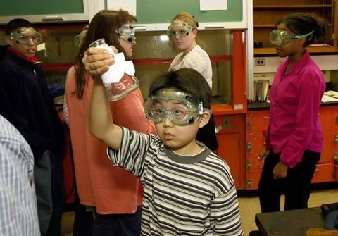 Freshman Sho Yano, 9, checks his beaker during a chemistry class experiment in Sept., 2000.