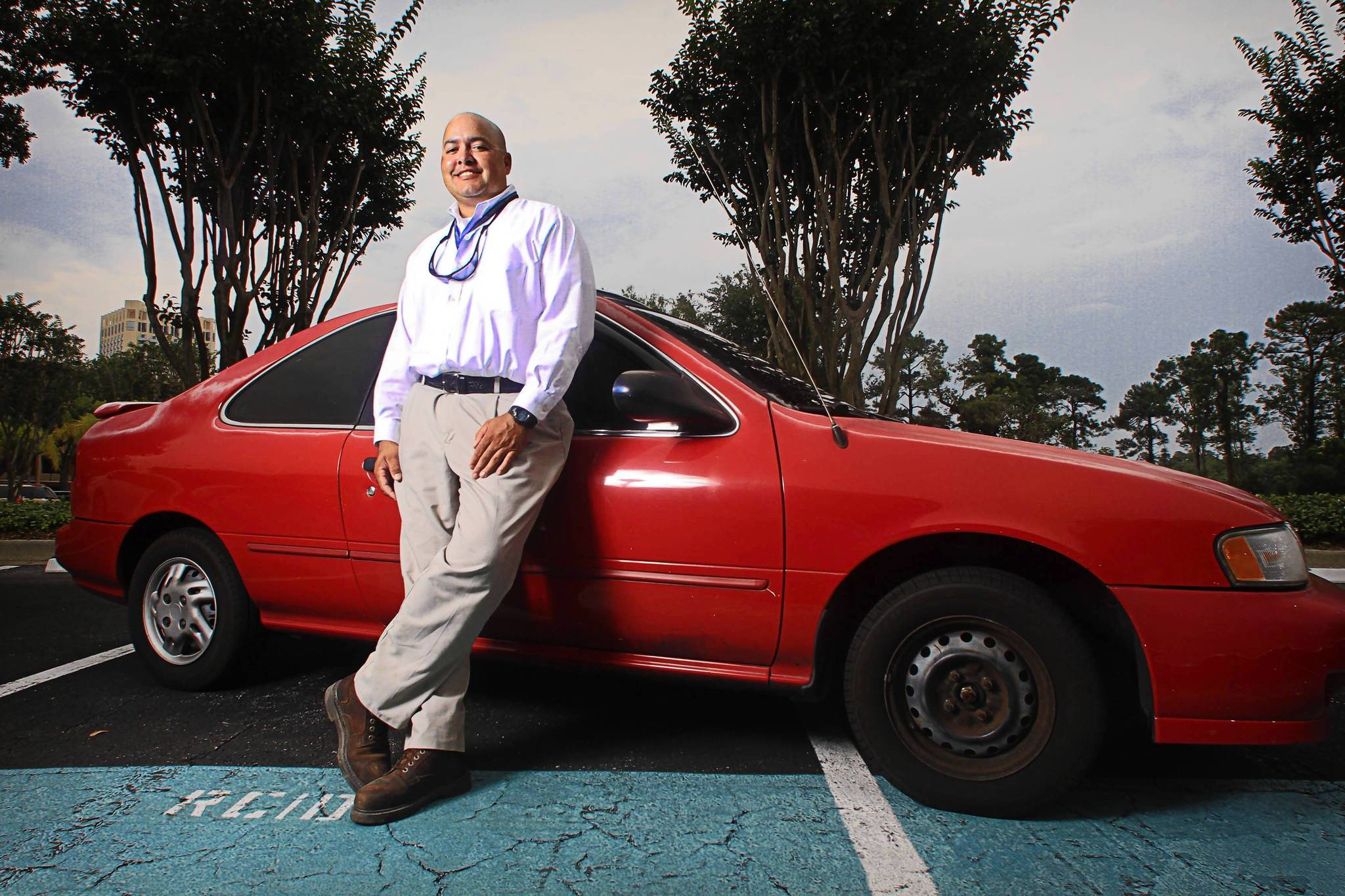 Jose Rodriguez poses near his older car, a 1995 Nissan 200SX with 295,000 miles on the odometer.