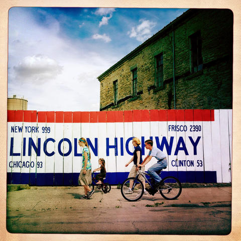 The Van Raden family passes a painted fence at the Lincoln Highway Association National Headquarters on Lincoln Highway in Franklin Grove.