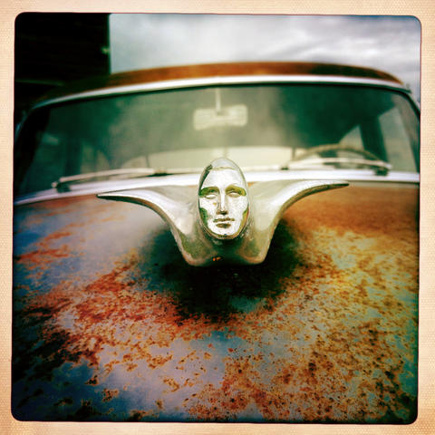 The hood ornament on an old Cadillac in front of a barn on Lincoln Highway in Rochelle.