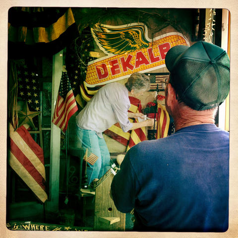 """Art Waters watches as his wife Joyce tweaks the window display at her shop, """"My Favorite Things"""", on Lincoln Highway in Dekalb"""