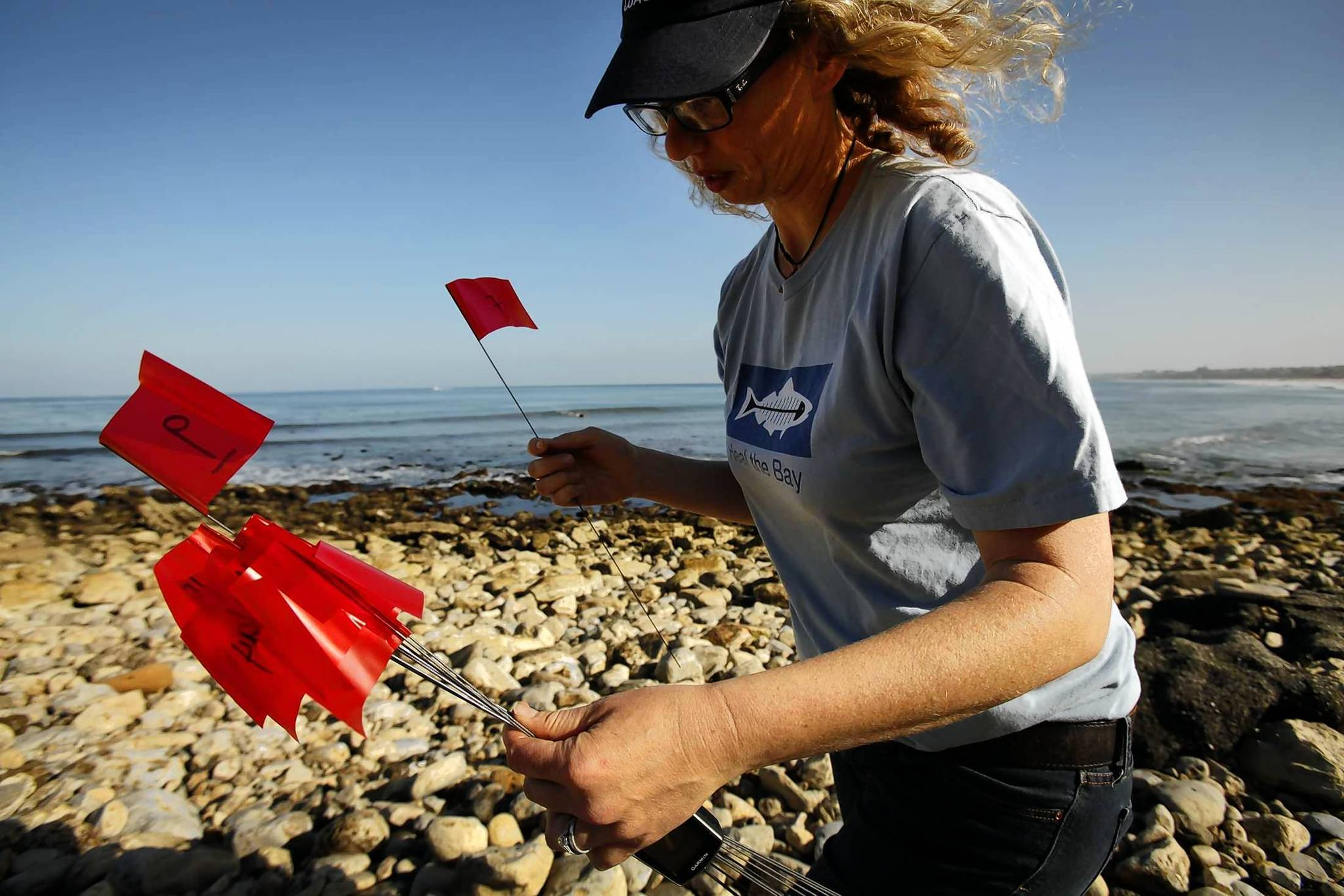 Meredith McCarthy, director of programs with Heal the Bay, places red flags on a 100-meter stretch of beach at Malaga Cove in Palos Verdes Estates on Friday morning.
