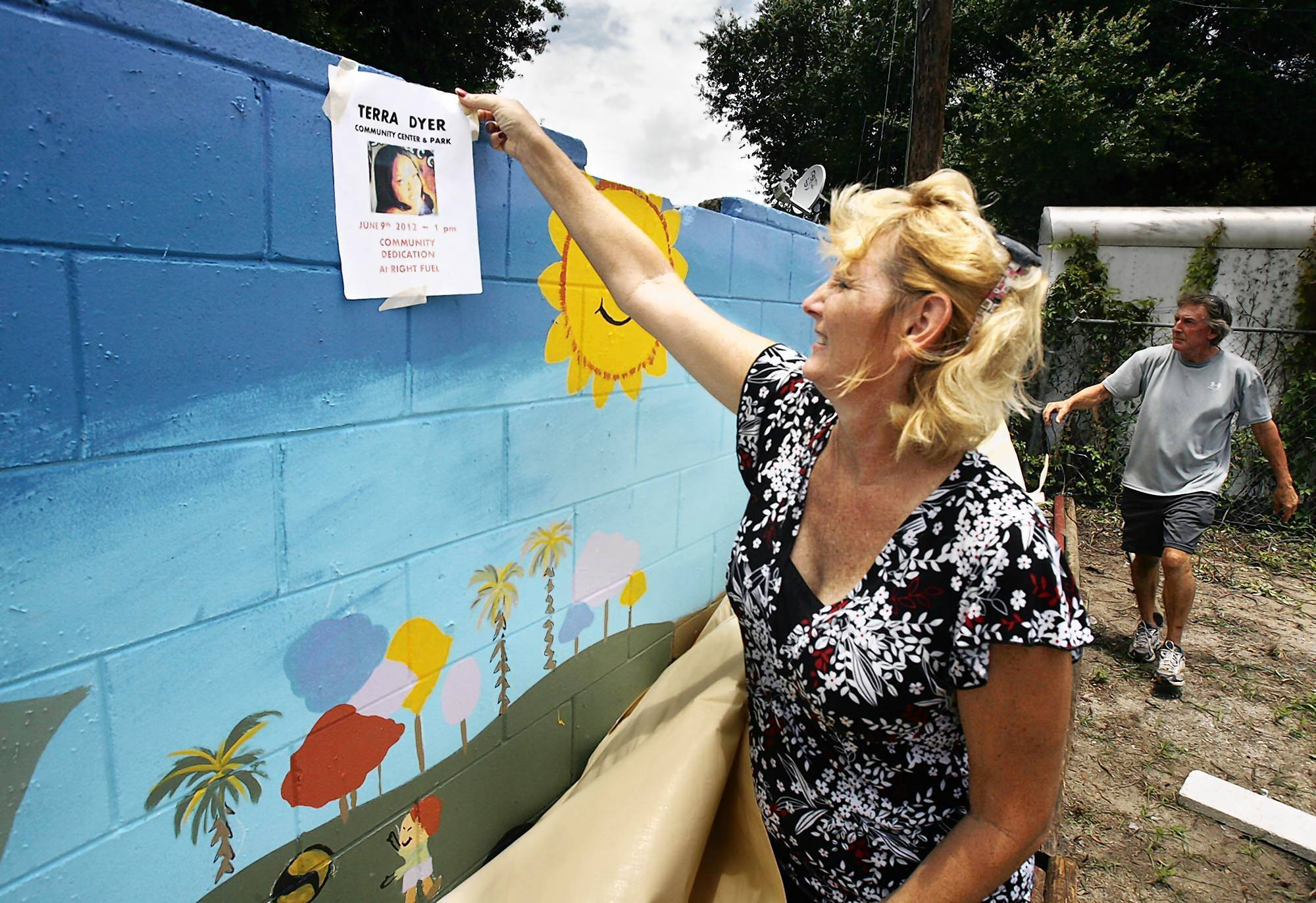 Rebecca Rae unveils a mural painted on a wall during a dedication ceremony for a community park in the Holden Heights community on Saturday. The park is dedicated to Terra Dyer, an 18-year-old woman who was killed nearby.