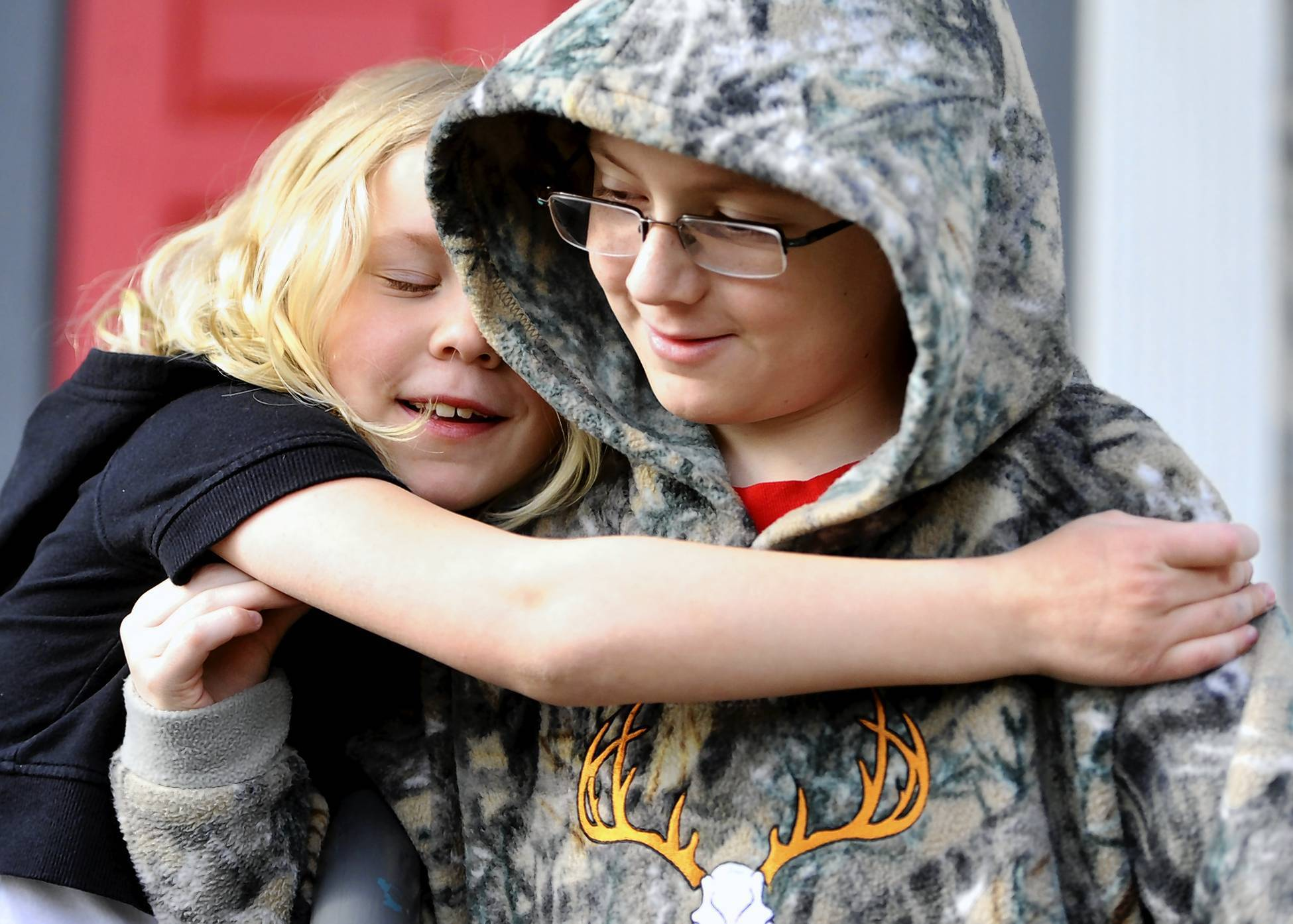Tommy Coykendall gets a hug from sister Hailey, 7, outside the Cancer Support Community.