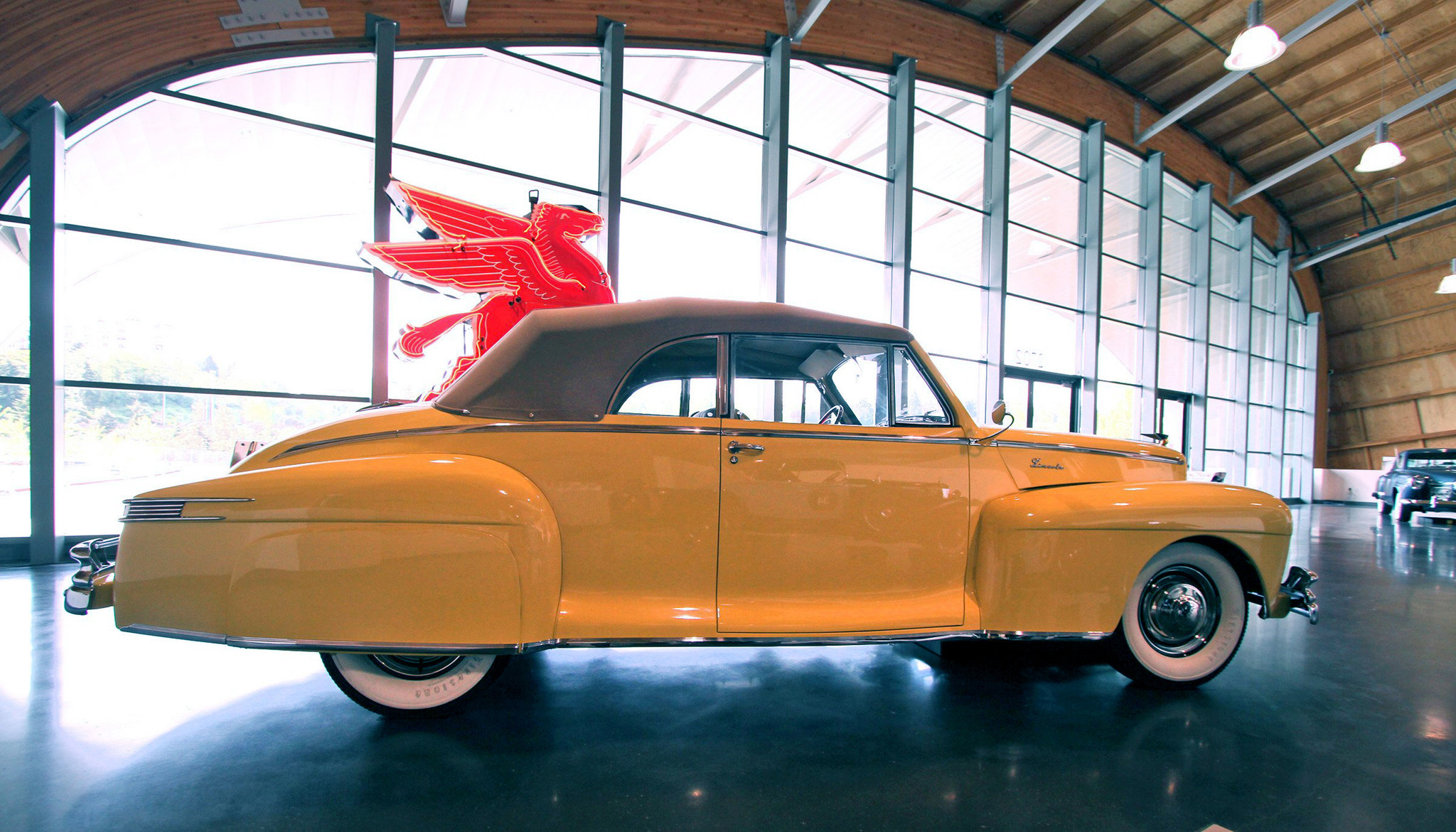 On display near the entrance is a gleaming 1947 yellow Lincoln convertible at LeMay car museum in Tacoma, Washington.
