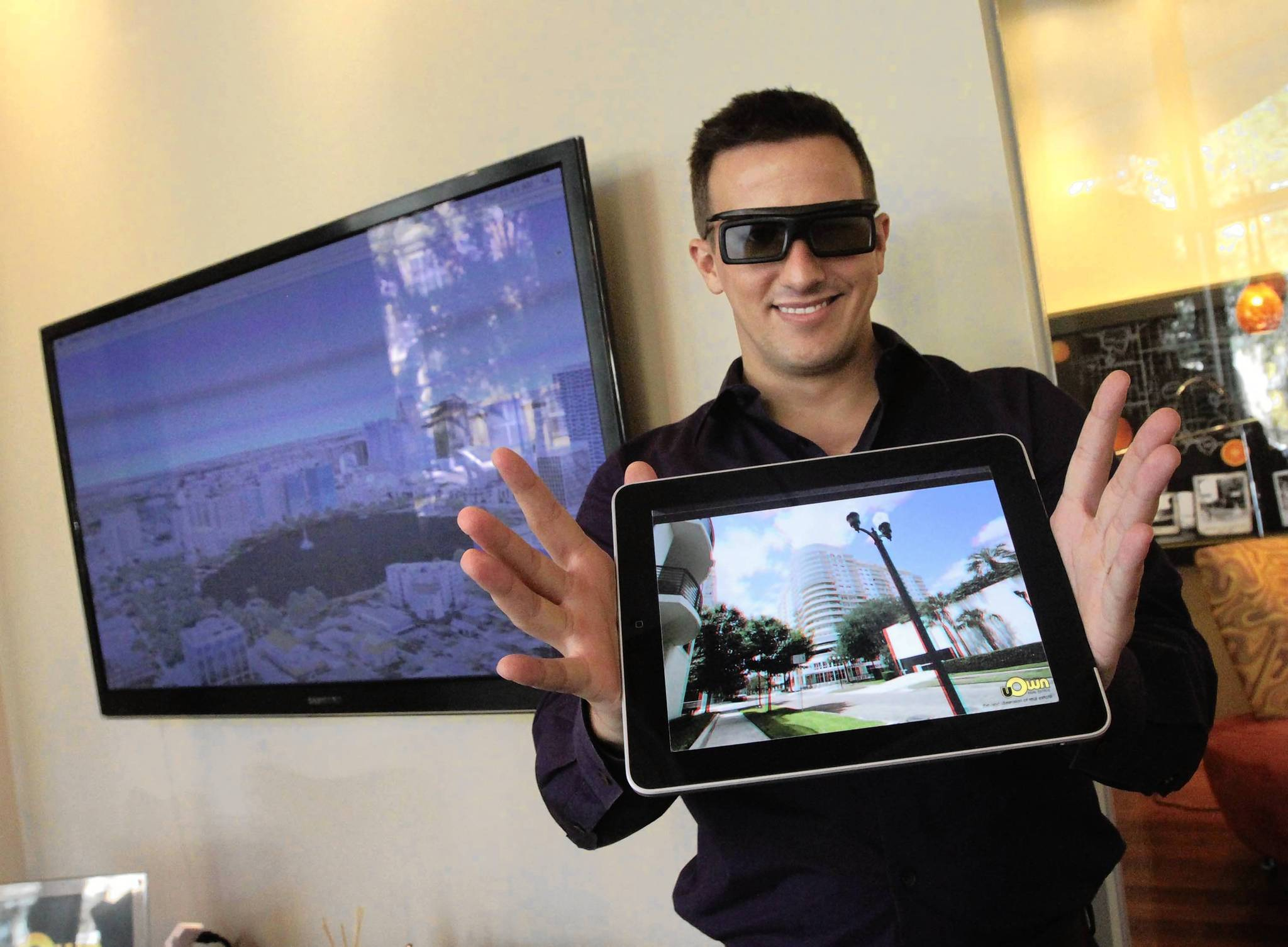 Sean Frank, owner of Orlando-based uOwn Real Estate, holds a tablet with double image to see with 3D glasses. He will be mailing fliers with cardboard 3D glasses so residents can view an online 3D photo gallery of Orlando landmarks on his website.