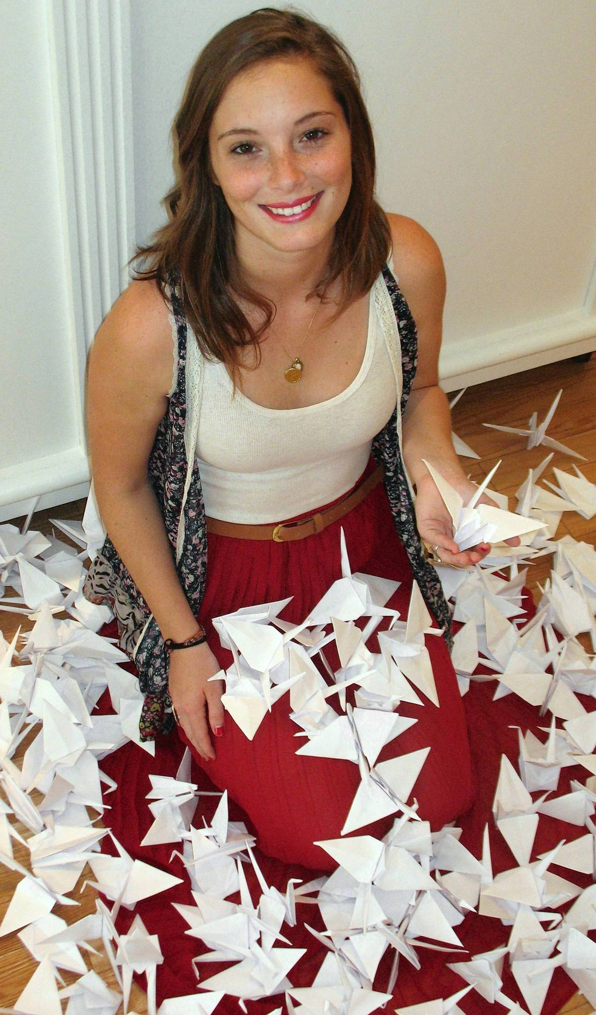 Artist Shaina Collier with white Japanese origami cranes.