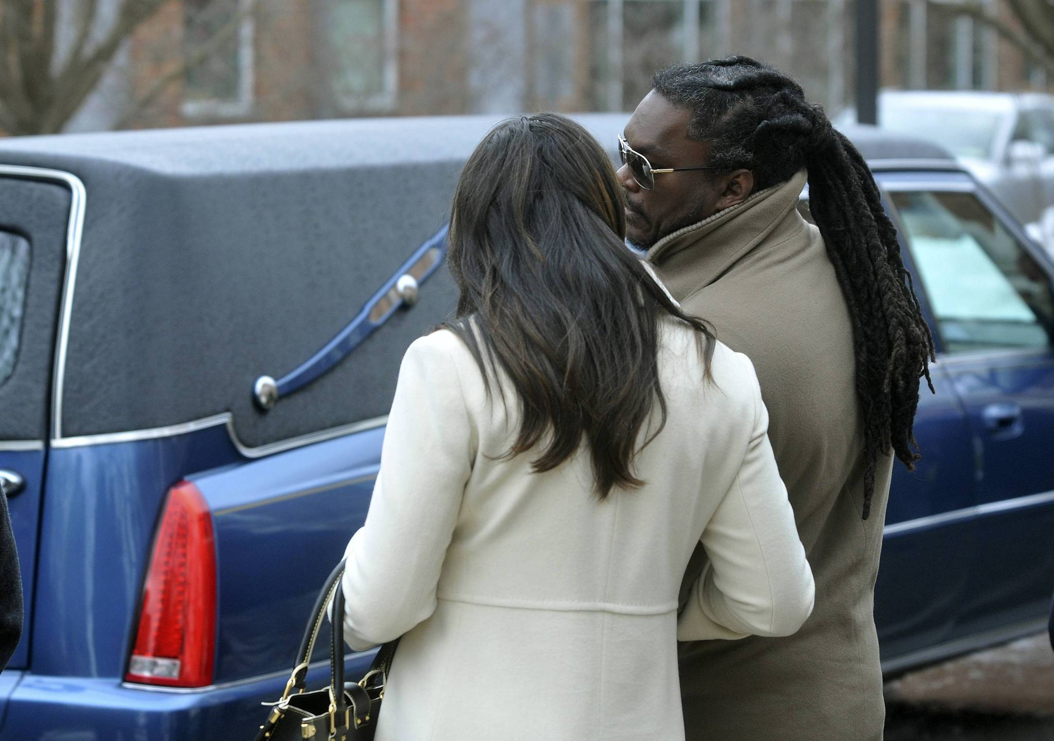 Former Penn State and Washington Redskins NFL linebacker LaVarr Arrington (R) passes by the hearse of former head football coach Joe Paterno. Mourners of Paterno are adjusting to life without the man who was the face of the university for half a century while coming to terms with a legacy tainted by his inactive role in a child sexual abuse scandal.