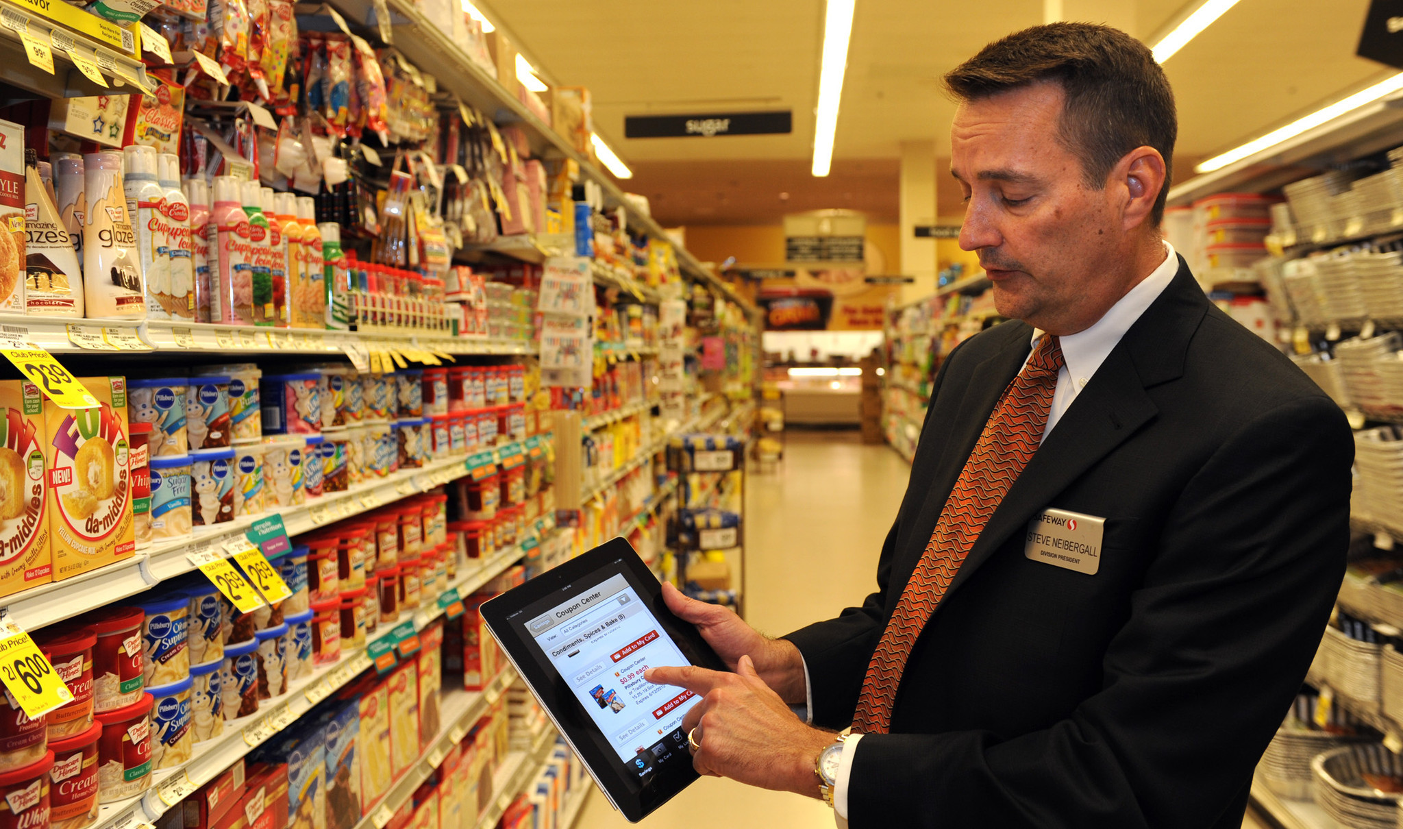 Steve Neibergall, president of Safeway's eastern division, demonstrates the company's new mobile app in the Canton store.