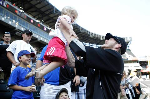 Sox pitcher Chris Sale picks up 3-year-old Adeline Rasnik, who was wearing a Cubs t-shirt, during batting practice.