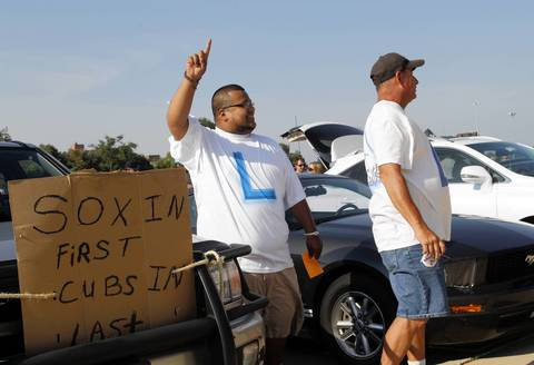 Enrique Delgado and Jerry Rocco display their feelings about the Cubs while tailgating.