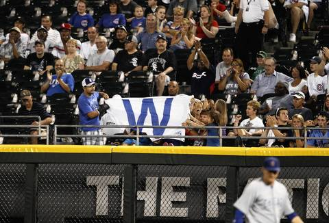 Cubs fans unfurl the victory flag after the 12-3 win.