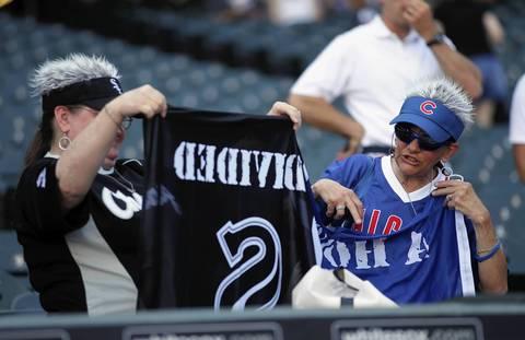 Sox fan Marie Fobes and Cubs fan Peggy Sotlin try to get their flag unfurled before the game.