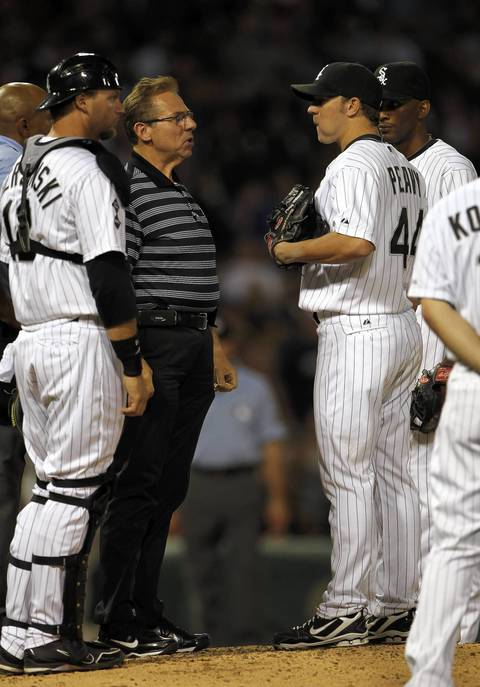 Sox trainer Herm Schneider chats with Jake Peavy in the 9th inning.