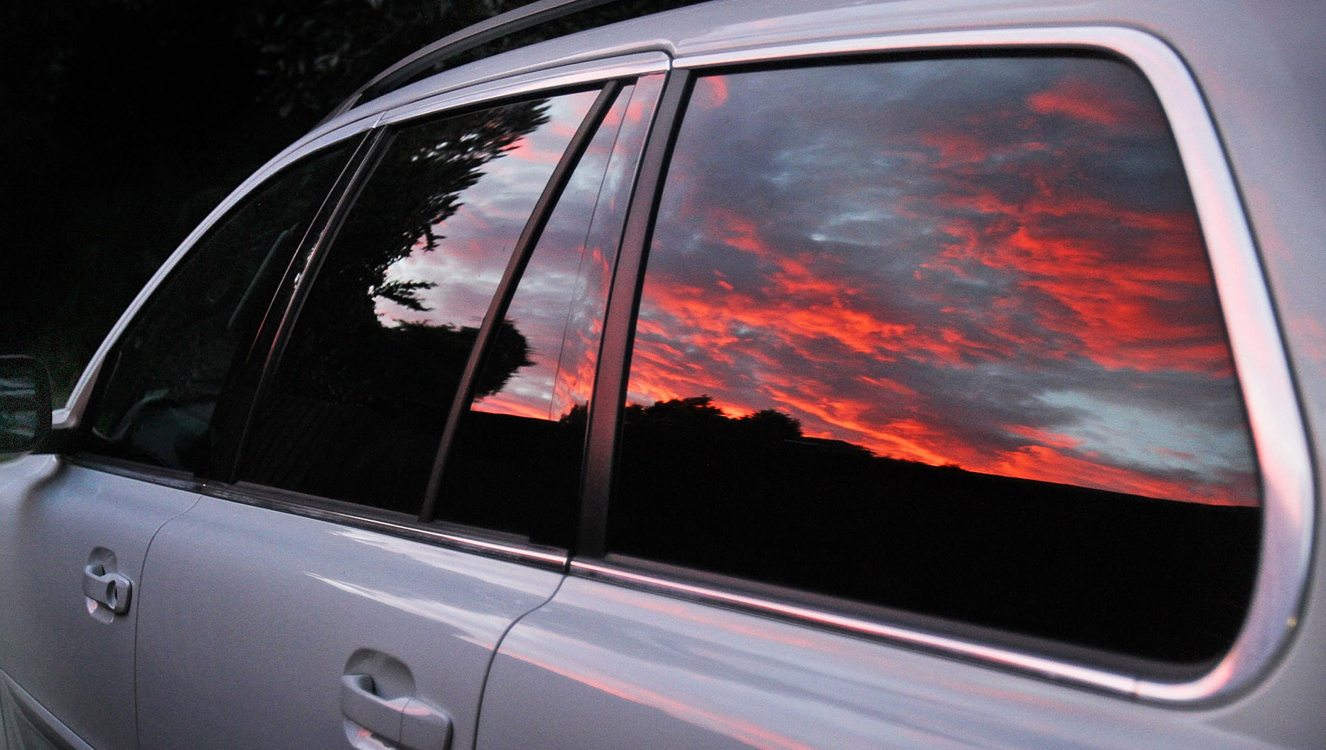 A dramatic sunrise sky is reflected in a car's windows on June 20, 2012.
