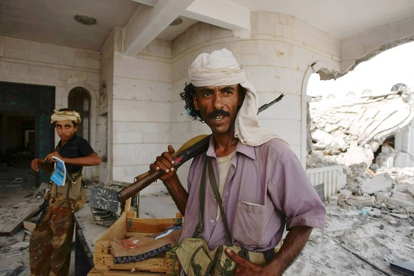 A Yemeni tribesman stands next to a destroyed government building in the southern city of Zinjibar, where the military had battled Al Qaeda militants.