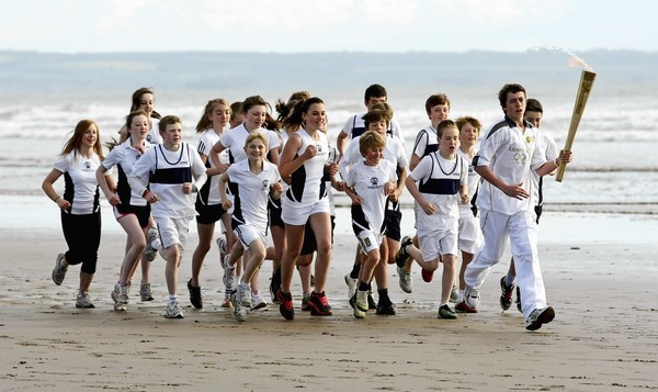 ST ANDREWS, SCOTLAND - JUNE 13:  In this handout image provided by LOCOG, Torchbearer 002 Joseph Forrest and children from Madras College, run along West Sands beach with the Olympic Torch during the London 2012 Olympic Torch Relay on June 13, 2012 in St Andrews, Scotland. The Olympic Flame is now on day 26 of a 70-day relay involving 8,000 torchbearers covering 8,000 miles.