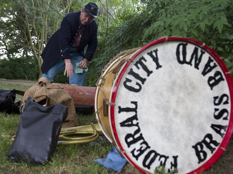 Eric Pfeiffer packs up an E-flat alto horn following a performance by the Federal City Brass Band to commemorate the 150th anniversary of Taps at Berkeley Plantation in Charles City on Friday.