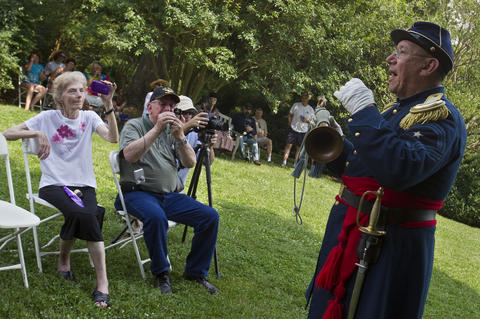 Jari Villanueva, Principal Musician of the Federal City Brass Band, describes the historical and modern importance of Taps to a crowd at Berkeley Plantation in Charles City on Friday.