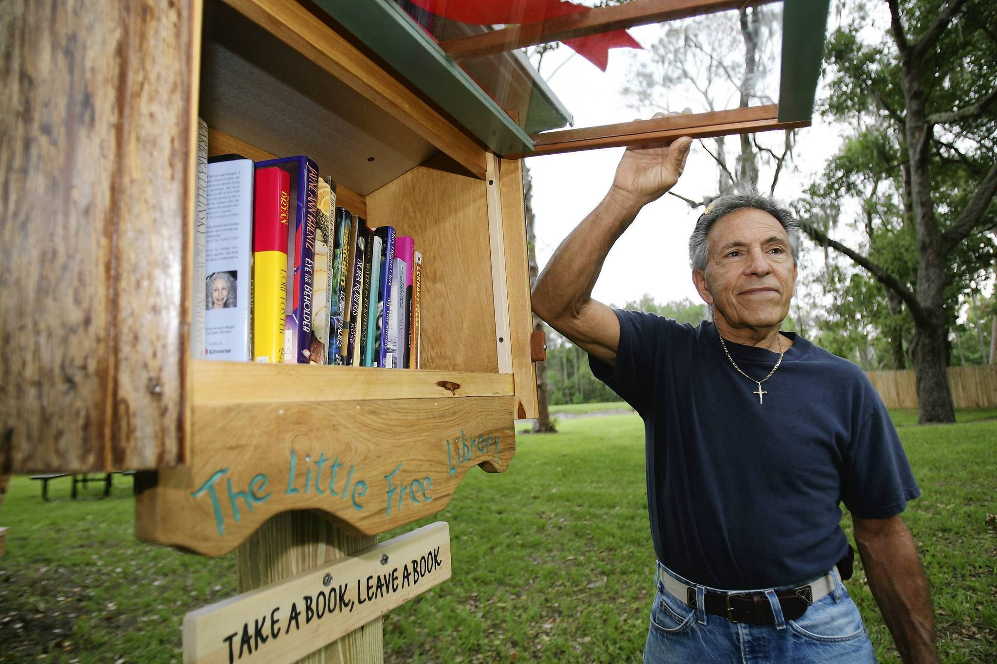 Artist Corado Vittoria poses with the library station he designed and built, during a ribbon-cutting ceremony on Wednesday, June 6, 2012, for the  Little Free Library station at  Aesop's Park in Tavares . (Tom Benitez/Orlando Sentinel