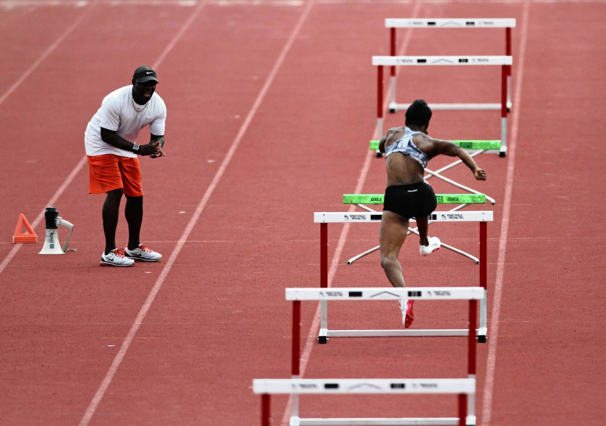 Three-time Olympian Dennis Mitchell, left, is training a group of international athletes for the upcoming Olympic trials and summer Olympics, including USA hurdler Kellie Wells, at right, at the National Training Center in Clermont, Fla. Thursday, June 7, 2012.   (Gary W. Green/Orlando Sentinel) ORG XMIT: B582153988Z.1