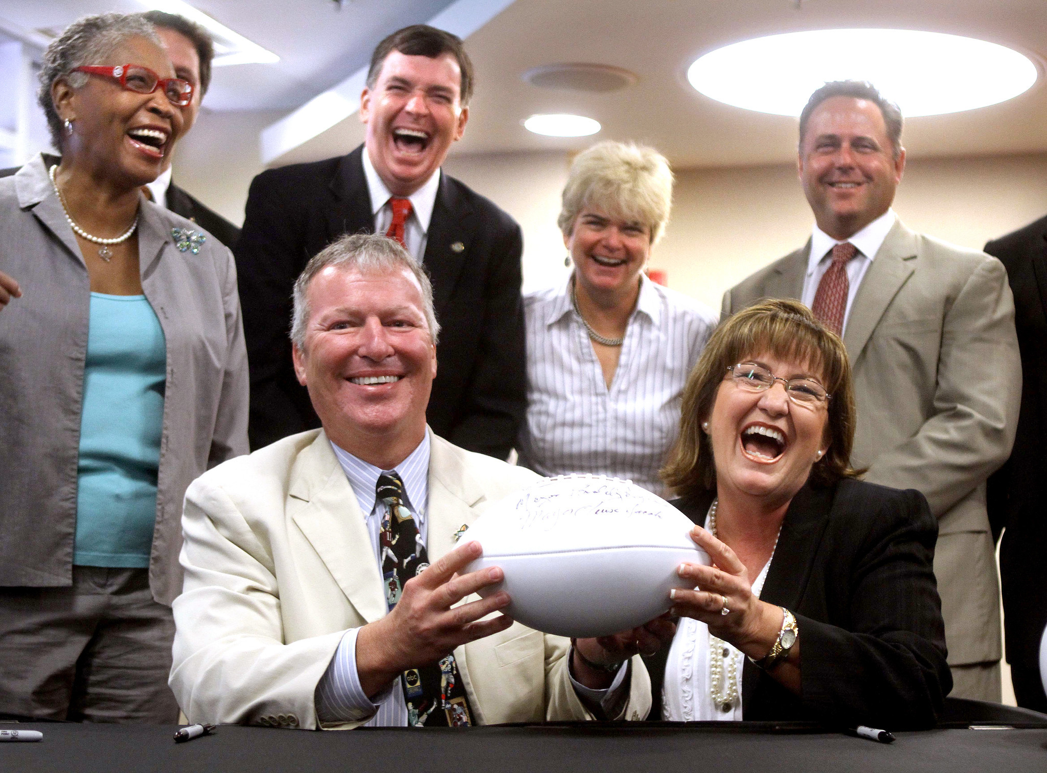 Orlando mayor Buddy Dyer, Orange mayor Teresa Jacobs and commissioners, from left, Daisy Lynum, Robert Stuart, Patty Sheehan and Scott Boyd, enjoy the moment as a deal for renovation of the Florida Citrus Bowl is officially  announced Monday, June 25, 2012, during a press conference at the stadium.