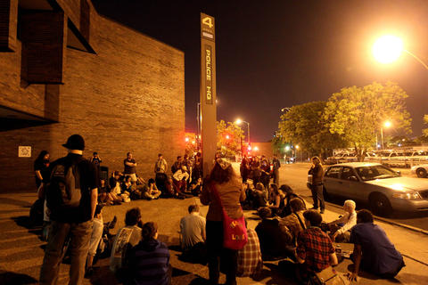 Occupy Chicago protesters have a group discussion in front of Chicago Police Department's Area 4 headquarters at Harrison and Kedzie as they wait for the release of three more detained protesters.