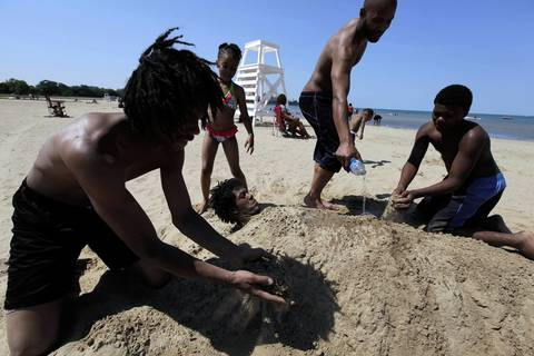 Family members bury Lonnell Taylor of Chicago in sand on the 63rd Street beach.