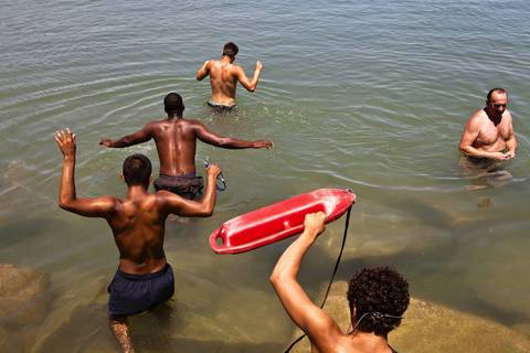 A group of friends enjoy swimming at the Promontory Point in Hyde Park.