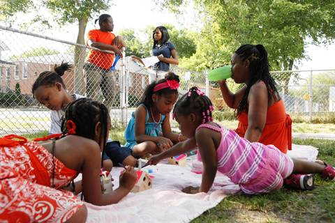 Hilda Prado-Maddox, seated at right, hosts a front yard seventh birthday party for her granddaughter Myshona Prado-Banks, seated third from left, as they escape the hot weather and paintsellphoto birdhouses under a shade tree at their Evanston home.